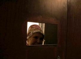 В Николаеве пенсионерка продавала самогон через отверстие в двери своей квартиры